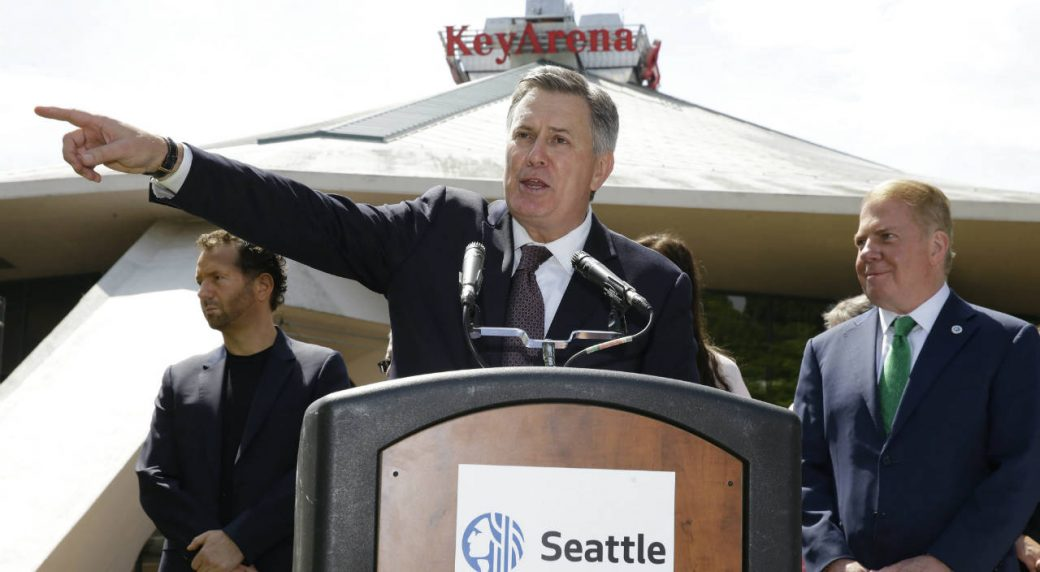 Tim-Leiweke,-CEO-of-the-Oak-View-Group,-centre,-speaks-during-a-news-conference-as-Seattle-Mayor-Ed-Murray-looks-on-at-right-on-Wednesday,-June-7,-2017,-in-front-of-KeyArena-in-Seattle.-Murray-said-the-city-will-enter-into-negotiations-with-the-Oak-View-Group-on-a-proposal-for-a-privately-financed-renovation-of-the-city-owned-KeyArena.-Plans-for-the-remodel-would-bring-the-building-up-to-standards-that-could-attract-an-NHL-or-NBA-franchise-once-completed.-(Ted-S.-Warren/AP)