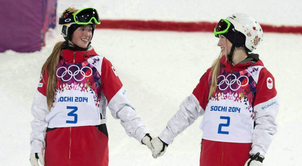 Canada's-Justine-Dufour-Lapointe-and-Chloe-Dufour-Lapointe-holds-hands-before-climbing-on-the-podium-after-winning-the-gold-and-silver-medals-in-the-moguls-at-the-Sochi-Winter-Olympics-Saturday-February-8,-2014-in-Sochi,-Russia.-(Adrian-Wyld/CP)
