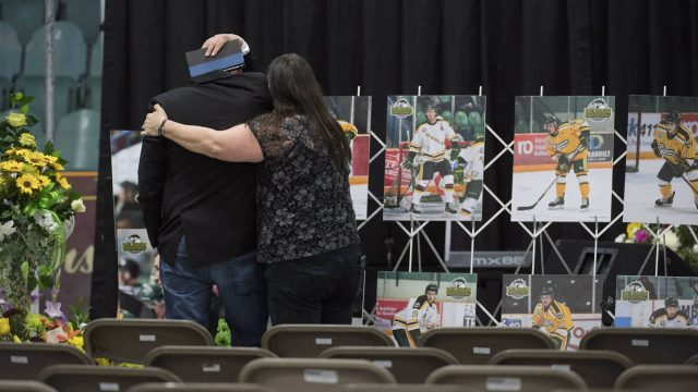 A-man-is-comforted-as-he-looks-at-photographs-prior-to-a-vigil-at-the-Elgar-Petersen-Arena,-home-of-the-Humboldt-Broncos,-to-honour-the-victims-of-a-fatal-bus-accident-in-Humboldt,-Sask.-on-Sunday,-April-8,-2018.-(Jonathan-Hayward/CP)