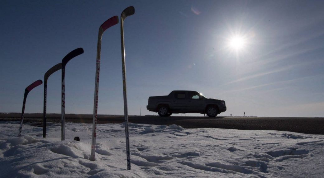 Hockey-sticks-to-remember-members-of-the-Humboldt-Broncos-are-silhouetted-against-the-morning-sun-along-a-stretch-of-highway-6-in-Saskatchewan,-Friday,-April,-13,-2018.-Today-there-is-a-public-memorial-for-18-year-old-Parker-Tobin,-20-year-old-Jaxon-Joseph,-18-year-old-Logan-Hunter-and-21-year-old-Stephen-Wack,-players-with-the-SJHL-Humboldt-Broncos-who-were-among-those-killed-when-the-team-bus-and-a-semi-truck-collided-at-an-intersection-in-rural-Saskatchewan.-(Jonathan-Hayward/CP)