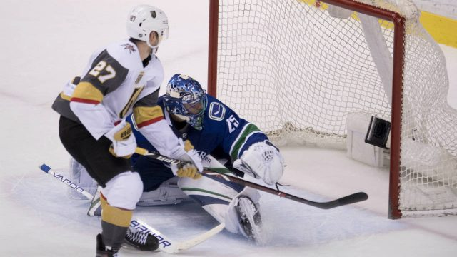Vegas-Golden-Knights-defenceman-Shea-Theodore-(27)-scores-past-Vancouver-Canucks-goaltender-Jacob-Markstrom-(25)-for-the-winning-shootout-goal-in-NHL-action-at-Rogers-Arena-in-Vancouver,-Tuesday,-April,-3,-2018.-(Jonathan-Hayward/CP)