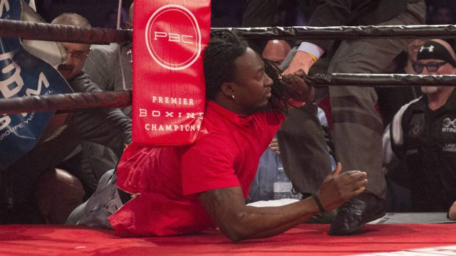 An-Ontario-boxing-commission-official-tries-to-remove-a-fan-from-the-ring-during-a-fight-on-the-undercard-of-the-Adonis-Stevenson-Badou-Jack-boxing-card-at-the-Air-Canada-Centre-in-Toronto-on-Saturday,-May-19,-2018.-A-spokesman-for-the-promoter-said-the-spectator-had-over-imbibed-and,-thinking-the-bout-was-boring,-wanted-to-liven-it-up-by-getting-into-the-ring.-(Frank-Gunn/CP)