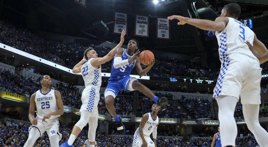 ef4fb4c171f Duke forward RJ Barrett (5) shoots around Kentucky forward Reid Travis (22)  during the first half of an NCAA college basketball game at the Champions  ...